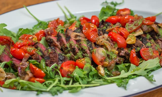 Grilled Marinated Flank Steak with Blistered Tomatoes and Basil Vinaigrette is the perfect meal for easy entertaining. #steak #flanksteak #grilling #tomatoes #arugula