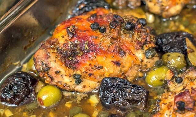 Chicken Marbella, a classic dish, is chicken roasted with garlic, olives, capers, and prunes. It's the perfect meal for a large dinner party. #dinnerparty #chicken #chickenrecipe
