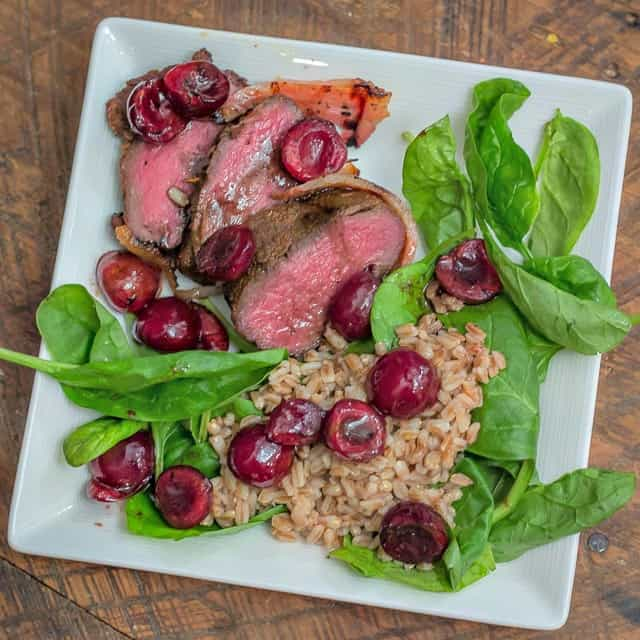 Grilled Bacon-Wrapped Venison Backstrap with Balsamic Cherries and Farro