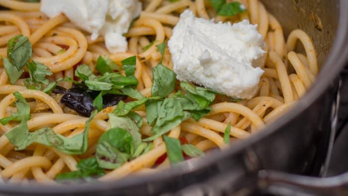Adding fresh ricotta and basil to the Pasta Alla Norma