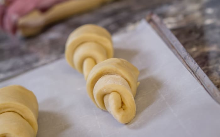 Place the rolled crescents on a baking sheet covered with parchment paper.