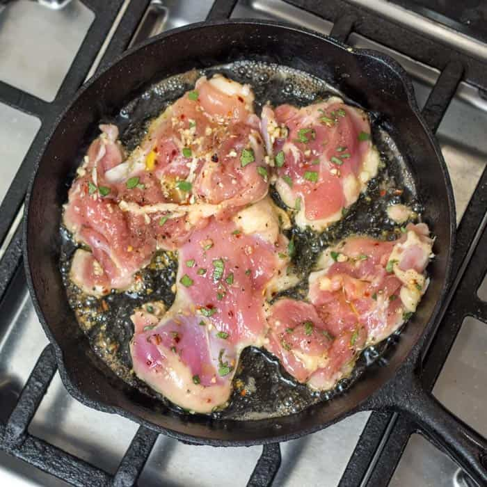 My pounded, marinated chicken thighs are browning in my cast iron skillet.