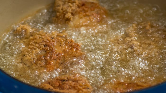 The chicken needs to cook covered in the Dutch oven for 10 minutes. Then, you fry until it's golden brown, and remove it from the oil, where you check to make sure it has reached 160º.